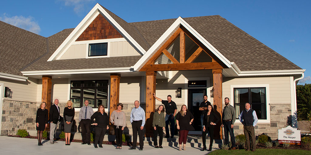 The Demlang team standing in front of The Harper model home